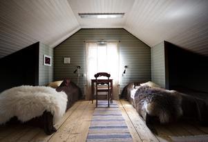 På övervåningen finns ett vackert inrett sovrum – även det målat med äggoljetemperafärger. Vindsgarderoberna är borttagna och där finns i stället plats för två extra bäddar.