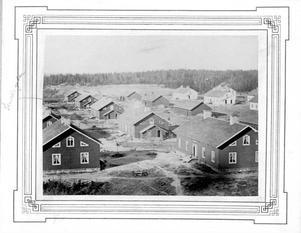 SANDVIKEN VÄXER FRAM. Utsikt över Smedsgatan från 1870-talet. Arbetare behövdes och genom att erbjuda förmånliga villkor för familjer såsom bra löner och bra boende var det möjligt att attrahera den mest kvalificerade arbetskraften. Det beslutades redan i början att alla arbetare skulle egna lägenheter med ett rum och kök och egen ingång. Varje familj hade också en del i en trädgård för att odla grönsaker.Bilden är från konsul Göranssons fotoalbum. Foto: Sandvikens kommunarkiv och Sandviks historiska arkiv.