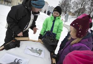 Barnen väljer hur de ska designa sin dinosaurie tillverkad i snö.