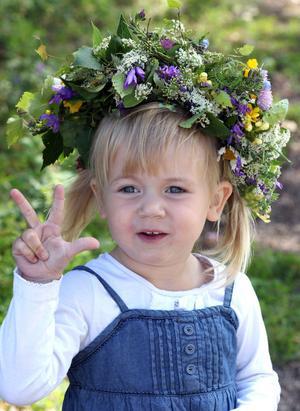 MIDSOMMARTJEJ. Treåriga Nova Setterlund har en välbunden blomsterkrans i håret som mormor har gjort.