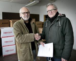 """2014 överlämnade Anders Pettersson från ABF Nordöstra Storstockholm, till höger, ett gåvobrev för Brunnsviksböckerna till Ingvar Henriksson (S). Sedan dess har böckerna förvarats i Gruvkontoret i Grängesberg men har nu återbördats till """"Bokstugan"""" på Brunnsvik."""