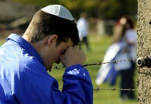 En judisk pojke ber en bön vid dödslägret Auschwitz-Birkenau, till minne av förintelsens offer, 2009. (AP Photo/Alik Keplicz)