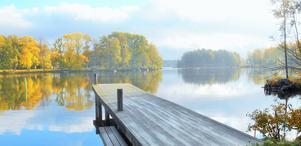 Oktobermorgon dimman som låg över sjön har precis dragit bort och solen visar de vackra färger som höstträden visar upp.