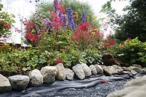 En konstgjord bäck rinner genom trädgården.