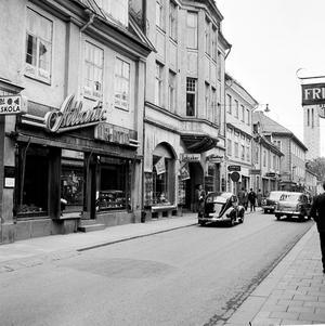 Före Sigma. Lundbergs Eftr hette en delikatessbutik på Köpmangatan, med ingång från portalen där Folkvagnen är parkerad. Där ligger Sigma i dag. I Köpmangatans förlängning skymtar Stadshuset. Bilden är tagen på 1960-talet.