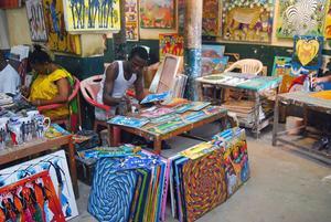 Konstformen Tingatinga har sitt ursprung i Dar es Salaam och på den stora inomhusmarknaden sitter konstnärerna och målar de färgglada motiven på löpande band.    Foto: Sofia Hallonsten