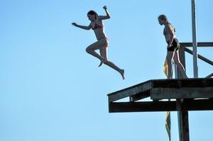 Tuffa tjejer hoppar. Tuffa tjejer hoppar från den högsta avsatsen medan kvällssolen sakta sänker sig bakom horisonten. Foto: Bengt Lövgren, Badelunda