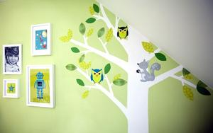 Egen design. Anna varvar foton och sina tryck i tavelramar på många väggar, här i sonen Viktors rum. Väggmålningen med trädet och ugglorna har Anna gjort själv. Ugglorna har hon skapat i dator, skrivit ut på vanligt papper och limmat på väggen med tapetklister.