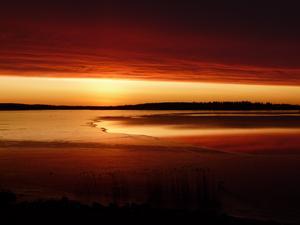 Västeråsfjärden en morgon med uppgående sol under tungt molntäcke. Fjärden delvis istäckt.