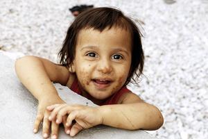 Aisha är 18 månader. Hon skrattar och busar. Och hon äter sopor från marken.