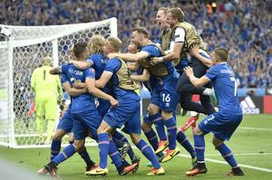 Island firar vilt efter att Arnor Ingvi Traustasons mål. Nummer 16 Rúnar Sigurjónsson befinner sig mitt i högen.