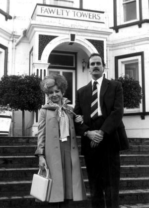 Prunella Scales som Sibyl Fawlty och John Cleese som Basil Fawlty utanför hotellet Fawlty Towers, där den ständigt farsartade handlingen utspelar sig i kultserien