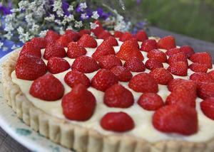 En fransk jordgubbstårta är låg, vid och fylld med både kräm och bär.