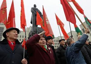 Demonstranter högtidlighåller minnet av oktoberrevolutionen vid den stora Leninstatyn framför parlamentet i Minsk.