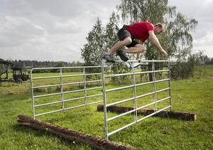 Henrik Josefsson häver sig över ett hinder gjort av en kogrind. Den ska täckas med en vägg så att ingen kan klättra över.