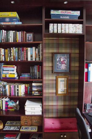 Bibliotek med rutig tapet och mörka hylllor för böcker och spel.