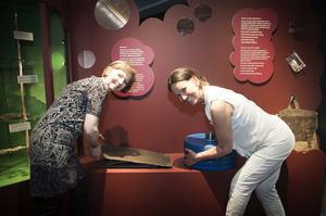 Gunilla Hedenblad och Ann-Sofie Axelsson visar på gamla tiders mynt och dess tyngd.