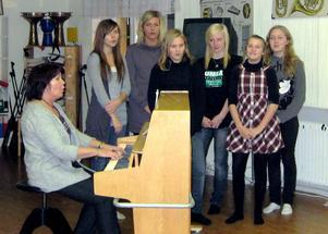 Flickorna Johanna, Angelica, Emelie R, Emelie I, Matilda och Maria tränar inför kyrkokonserten med sin lärare Gunilla.
