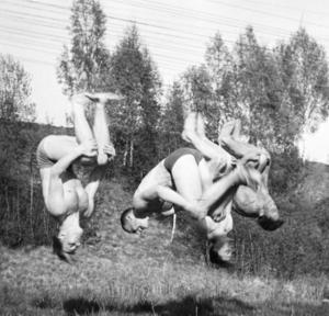 Mycket spex och skoj höll gymnasterna på med vid dåvarande klubbstugan vid Löten. Här testar de hur många som kan göra salto (volt bakåt) samtidigt. Gymnasterna heter Rolf Lindsköld, Janne Cronstedt, Bengt Fredborg och Gösta Diffner.