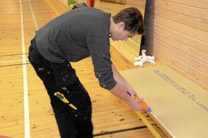 Lim. Alexander Pettersson limmade spånskivor i sporthallen. BILD: INGVAR SVENSSON