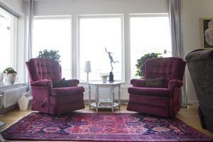 Mörka toner av rött och lila bryter av det ljusa i vardagsrummet.