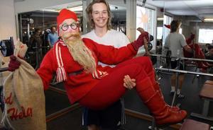 Fredrik Linder från Västerås, lyfter upp tomten som hälsar på inne på Friskis och Svettis. Fredrik brukar träna med sin syster Erika på julafton, i år är även pappa Sten med.