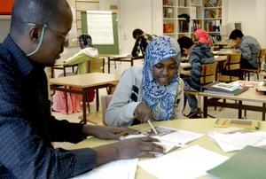 Modersmålsläraren Abdirahman Adan sitter vid sidan i klassrummet med eleven Farhia Muhammed och ger studiehandledning.