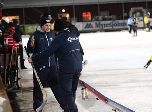 Assisterande tränaren Gustav Purvin och huvdtränaren Peter Rönnqvist kramar om varandra efter att ha säkrat en plats i elitserien.