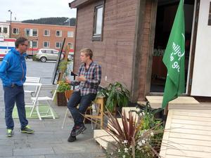 Miljöpartiets Anton Nordqvist framför valstugan som väl närmare får liknas vid en barack.