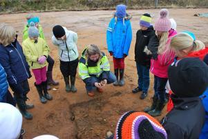 Arkeologen Anna Lögdqvist från Dalarnas Museum visar Åkeröelever rester av en eldhärd från 6500 år f Kr.
