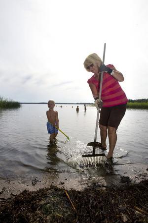 Lena Nordin slet hårt med räfsan i går. Här med tvååriga barnbarnet Ossie Solarinne.– Badet har sjangserat väldigt snabbt. Vi vill rädda vårt bad och hjälpa Tomas, säger hon.
