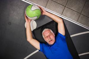 Tommy Nordin gör situps med en tung boll som barlast.