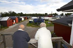 Dags att lägga i båten? Lennart och Hans blickar ut över uppläggningsområdet, där många båtar står under bar himmel i väntan på renovering.