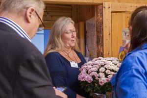Pia Enocson, ordförande i föreningen Loosgruvfan, tar emot grattisblommor från bygderådet.