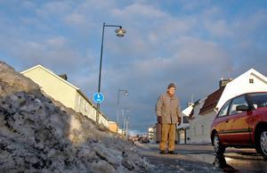 Ut i vägen. Tuve Säfström går själv med broddar och är inte rädd för att ramla. Men han vill att kommunen går något åt den stora snöhögen.