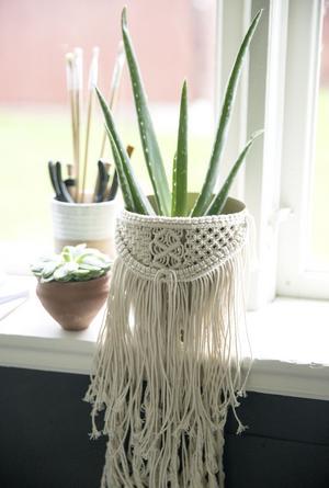 Även blommor som inte hänger i amplar kan få en snygg ytterkruka av makramé hemma hos Christel.