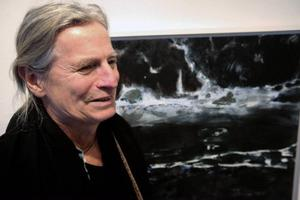 Magnus Berg framför en av flera målningar med en simmande figur, som han ställer ut på Galleri Remi just nu.