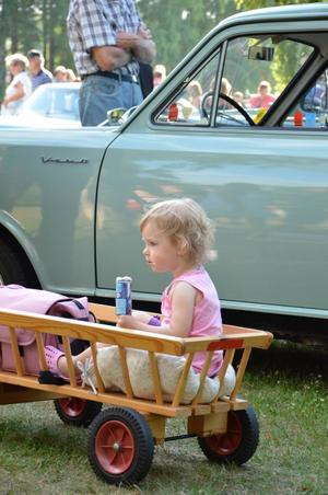 Bildtext: Selma Löfgren, 2 år, har parkerat sitt ekipage bredvid en Vauxhall Viva från 1964.