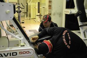 Trasiga maskiner. Jonas Pekkala, längst bort och Henrik Norberg lagade trasiga styrketräningsmaskiner.  BILD: INGVAR SVENSSON
