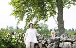 Anki Edlundh-Berglunds stora intresse är blommor. Här myser hon i trädgården med katten Smarties.