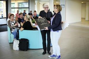 Annika Hagelin överlämnar pärmen med alla urklipp till Alirskolans rektor, Sibba Hanell.