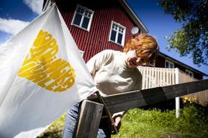 Annikka Arvidsson monterar en flagga utanför Järnsta Kafé.