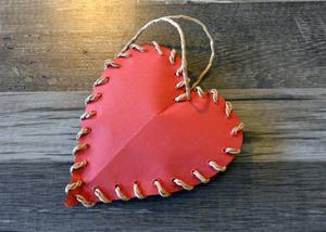Ett enkelt pappershjärta. Använd halvtjockt rött papper. Sätt bomullspads mellan de två bitarna. Gör hålen med hjälp av en stor nål och trä igenom tråden.