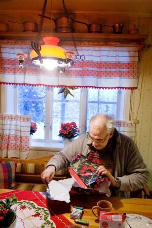 """Några julgåvor blev det för Gösta Olofsson i år. Lite choklad och ett par julgrupper låg under granen. Men den bästa julklappen var nog beskedet att Göstas bror kom för att hälsa på ett par dagar. """"Vi ses inte så ofta, därför känns det väldigt roligt att brorsan och hans hustru kom upp"""".    Foto: Ulrika Andersson"""