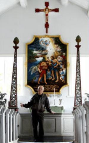Stig-Gunnar Wikberg, hamnfogde i Skeppshamns kapell, poserar i kapellet vid de nytillverkade kopiorna av krucifix och altartavlan som även den stulits.