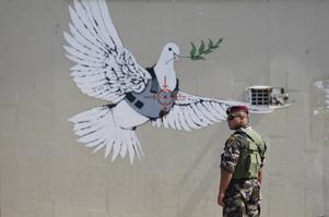 En man från den palestinska säkerhetsstyrkan bredvid en väggmålning som Banksy sägs ha målat, och som föreställer en fredsduva med skottsäker väst.   Foto: Mohammed Ballas/AP/TT