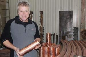 Företaget har investerat i en ny valsmaskin och planerar också att bygga ut sina lokaler. Här syns Lars Eriksson med kopparrör som valsats i den nya valsmaskinen.