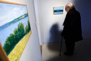 Anders Ek är tillbaka och ställer ut sina blå målningar på Galleri S. Torvalla by har bland annat stått modell för hans landskapsmålningar. Foto: Håkan Luthman