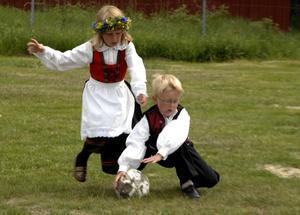 Natahlie Halvarsson, sju år, och Rasmus Lia, sex år, från Idre, värmer upp med fotboll inför majstångsresningen.