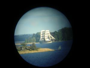 Briggen Tre Kronor för fulla segel utanför Östra holmen fotad genom teleskop.